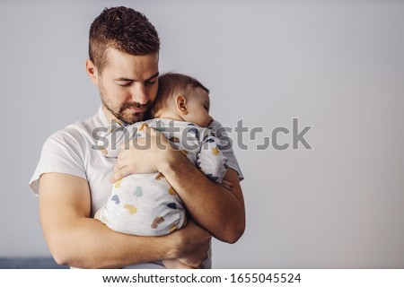 Handsome unshaven young father holding his only beloved son and putting him to sleep. It's noon nap time. Stock photo ©