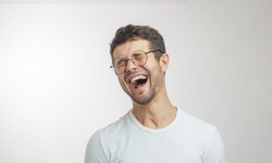 handsome unshaven young man laughing at a funny story facial expressions concept. isolated white background