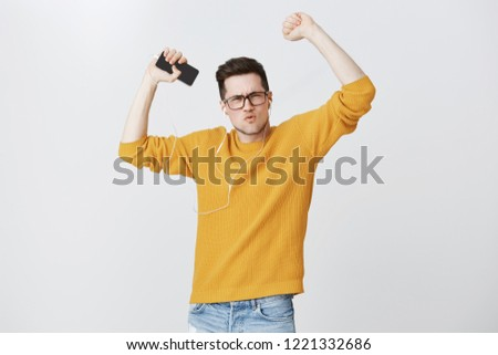 Handsome upbeat young european man in glasses and warm yellow sweater feeling like winner boosting energy and mood with cool music app, listening songs in earphones raising hands, aping over grey wall