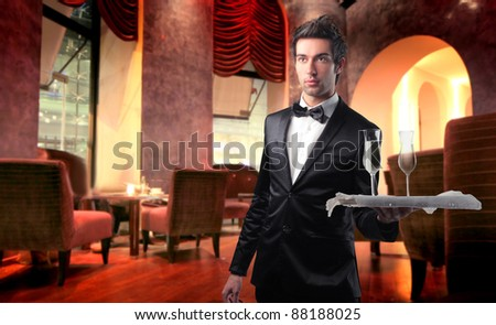 Handsome waiter serving wine glasses in a lounge bar