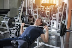 Handsome weightlifter lifting barbells bench press working out with curl bar in the gym.