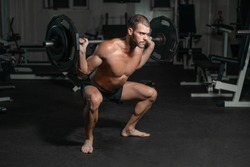 Handsome weightlifter lifting barbells with Squats. Male training with barbell, pumping legs