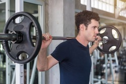 Handsome weightlifter lifting barbells with Squats smith machine working out in the fitness gym.