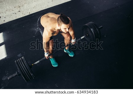 Handsome weightlifter preparing for training. Shallow depth of field, selective focus on hands and dust.