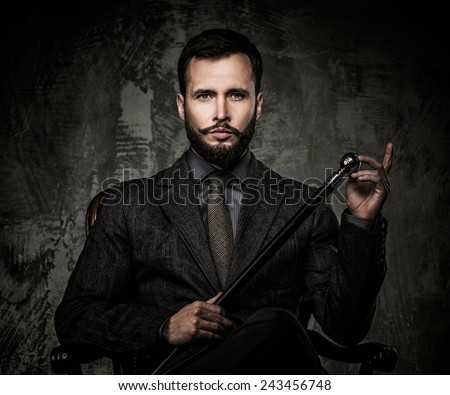 Handsome well-dressed man with walking stick sitting in leather chair  #243456748
