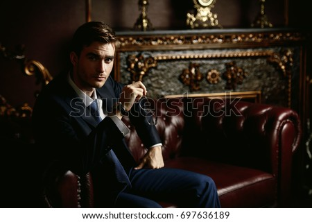 Handsome well-dressed young man in a room with classic interior. Business style. Luxury. #697636189