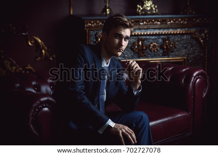 Handsome well-dressed young man in a room with classic interior. Business style. Luxury. #702727078