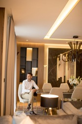 Handsome welldressed man sitting  in luxury house interior