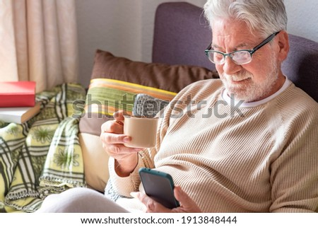 Handsome white-haired elderly man in lockdown at home using his smart phone while drinking a cup of coffee. Bright light from the window. Retired seniors using wireless technology Foto stock ©