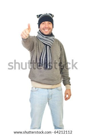 Handsome winter guy with knit cap and scarf giving thumbs up isolated on white background
