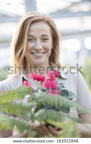 handsome woman holding one potted flowers in a garden center