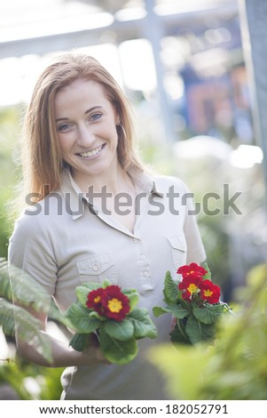 handsome woman holding two potted flowers in a garden center