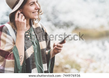 Handsome woman listening songs using her phone in first snow. Traveling among stunning winter landscape. Vacations in mountain wilderness. Wanderlust and boho style #744976936