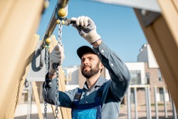 Handsome workman in uniform mounting swing on the playground outdoors