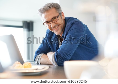 Handsome 45-year-old man at home connected on laptop Photo stock ©