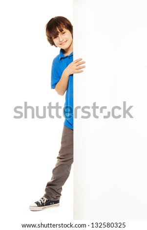Handsome 11 years old Caucasian boy, standing and smiling looking from behind white placard, isolated on white, full height portrait
