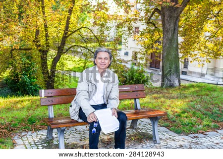Handsome 50 years old man with salt pepper hair and green eyes dressed with grey gabardine, linen white shirt and blue pants is reading documents in a park in Prague #284128943
