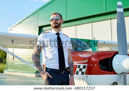 840d939e1fd Handsome young adult pilot in sunglasses posing at private motor airplane  on runway near hangar.