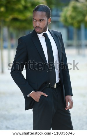 Handsome young African American business man in a black suit outdoors.