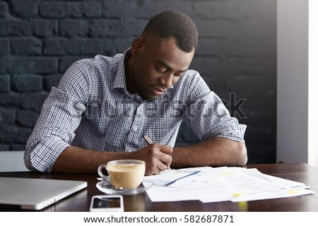 Handsome young African-American male student in shirt underlying important information in paper while preparing for lessons, sitting at University cafe with laptop and mobile phone, having coffee