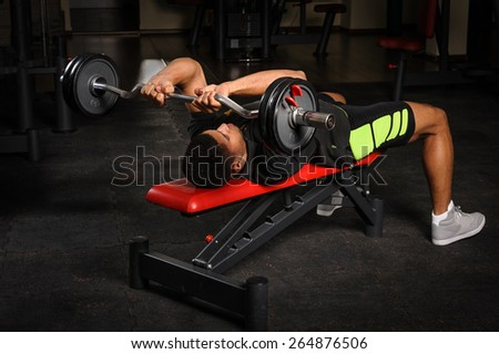 handsome young african descent mixed race man doing bench french press workout with barbell in gym