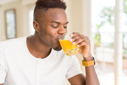 Handsome young african man drinking a glass of fresh natural orange juice enjoying fruit refreshment