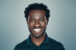 Handsome young African man looking at camera and smiling while standing against grey background