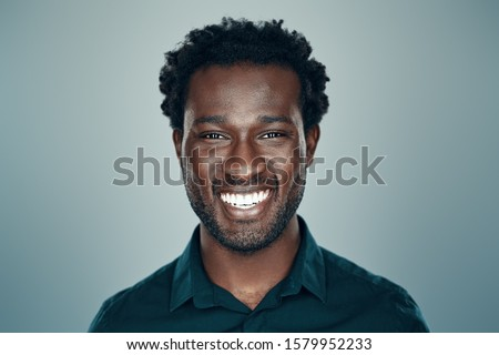 Handsome young African man looking at camera and smiling while standing against grey background                   Stock photo ©