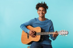 Handsome young african man playing a guitar while sitting isolated over blue