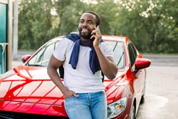 Handsome young African man wearing white t-shirt and jeans, talking on phone while leaning on his modern red car hood outdoors