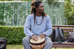handsome young afro man with djembe drums outdoors. african american man with dreadlocks sits on bench, perform music