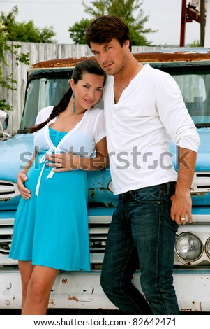 handsome young and expectant couple against vintage pickup truck