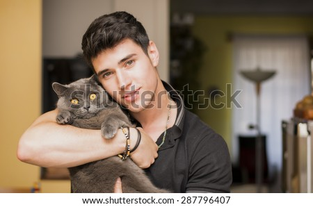 Handsome Young Animal-Lover Man Inside the House, Hugging his Gray Domestic Cat Pet.