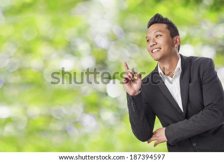 handsome young asian man pointing up with finger
