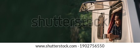 Handsome young Asian man, traveler on road trip, sit inside camping van in the morning. Cosy comfortable setup in camper trailer or van. Millennial travel trend, adventure on the road. Photo stock ©