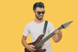 Handsome young asian men playing guitar and  listen music with headphones  isolated on yellow background