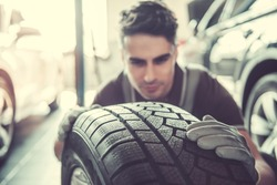 Handsome young auto mechanic in uniform is examining a tire while working in auto service