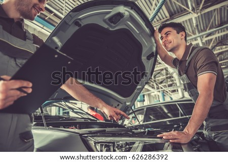 Handsome young auto mechanics in uniform are examining car while working in auto service #626286392