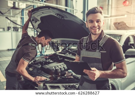 Handsome young auto mechanics in uniform are examining car while working in auto service #626288627