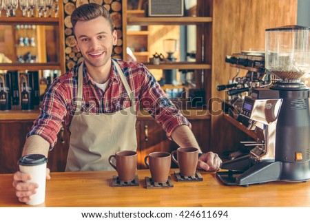 Handsome young barista in apron is giving a cup of coffee, looking at camera and smiling while standing at the bar counter at cafe