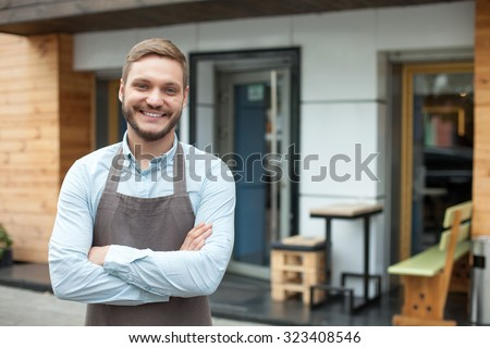 Handsome young barista is standing near his cafe outdoors. He is looking forward and smiling. The man crossed his arms with confidence