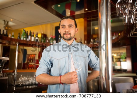 Handsome young bartender holds cocktail glass posing for camera. Bar employee being silly, thinking about work routine. Batirsta contemplating new drink recipes concept