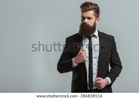 Handsome young bearded businessman in classic suit is adjusting his jacket and looking away, on a gray background