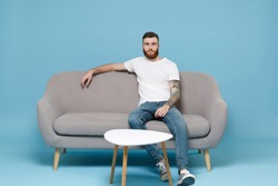 Handsome young bearded man guy in white blank empty t-shirt sitting on couch isolated on pastel blue wall background studio portrait. Sport leisure lifestyle concept. Cheer up support favorite team