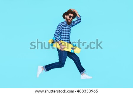 Handsome young bearded man jumping with yellow skateboard against the colorful wall. Hipster with beard in motion on blue background #488333965