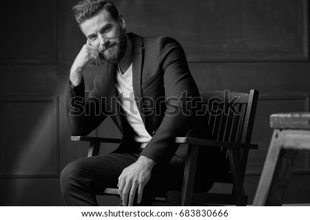 Handsome young beautiful and confident bearded man, wearing white shirt and brown jacket, sitting on wooden chair in studio with dark background and smiling, in black and white #683830666