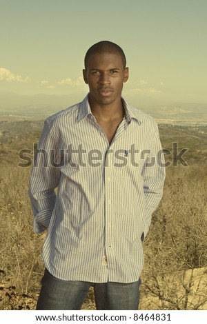 handsome young black man standing in a desert field