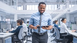 Handsome Young Black Manager in a Shirt Walking Pass His Business Colleagues with a Tablet and Supervise Their Work. Diverse and Motivated Business People Work on Computers in Modern Open Office.