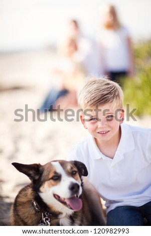 Handsome Young Boy Playing with His Dog at the Beach.