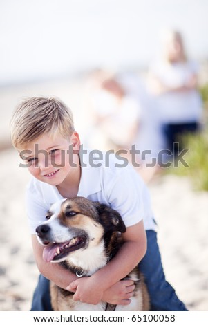 Handsome Young Boy Playing with His Dog at the Beach. - stock photo